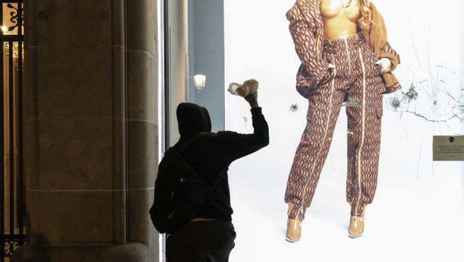 Un encapuchado aporrea el cristal de una tienda durante los altercados en Barcelona por el encarcelamiento del rapero Pablo Hasel.