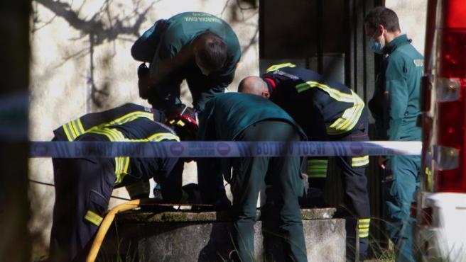 Guardias civiles y bomberos trabajan en el pozo donde fue hallado el cadáver de un hombre, en una finca de O Porriño (Pontevedra).