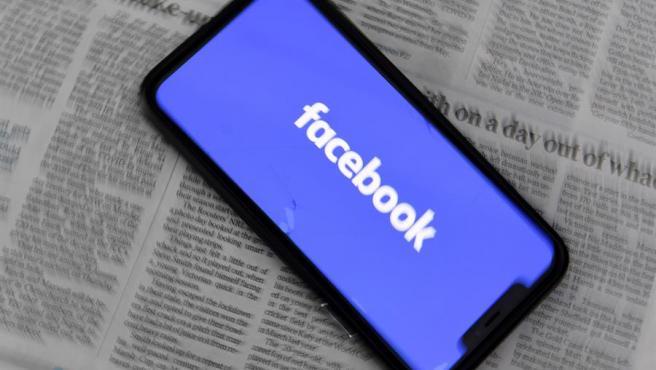 Un teléfono móvil con el logo de Facebook, colocado sobre las páginas de un periódico, en Canberra, Australia.