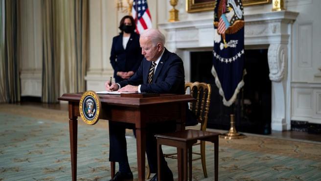 El presidente de EE UU, Joe Biden, firma una orden ejecutiva en la Casa Blanca, acompañado por la vicepresidenta, Kamala Harris.