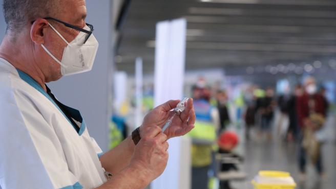 Un sanitario prepara una vacuna en el punto de vacunación contra el Covid-19 puesto en marcha en el Estadio Wanda Metropolitano el primer día de su funcionamiento, en Madrid (España), a 25 de febrero de 2021.