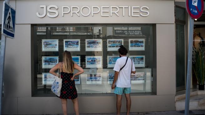 Archivo - Dos personas observan inmuebles en alquiler y en venta en un escaparate de una inmobiliaria ubicada en Palma.