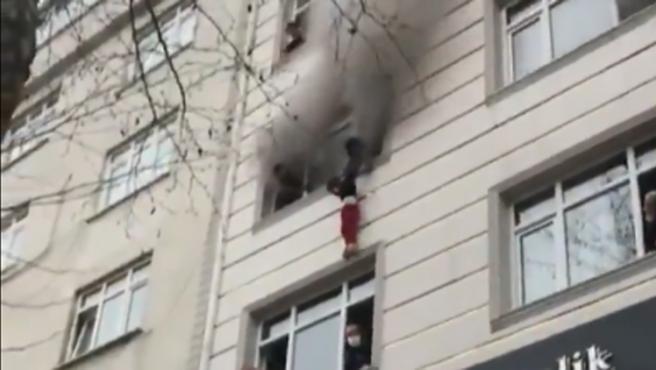 La madre se prepara a lanzar al menor por la ventana.