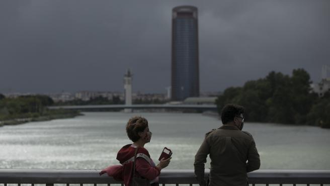 Dos personas caminan por el Puente de la Barqueta durante el aviso amarillo activado por la Agencia Estatal de Meteorología. (Aemet).