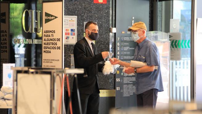 Un trabajador de El Corte Inglés reparte guantes a la entrada de un centro.