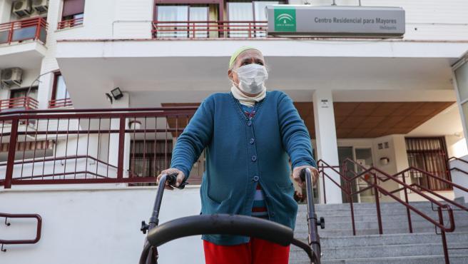 Una anciana sale de un centro residencial para mayores.