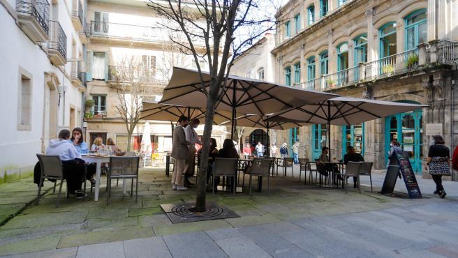 Varias personas en la terraza de un restaurante durante el primer día de la apertura parcial de la hostelería en Vigo, Pontevedra, Galicia (España), a 26 de febrero de 2021. La Xunta de Galicia reabre desde hoy parcia