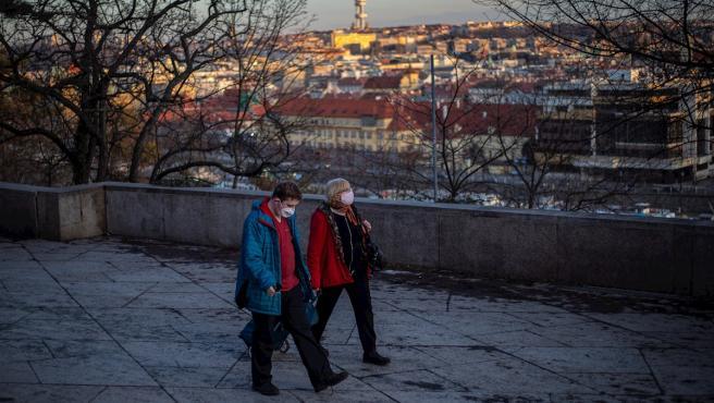 Dos personas pasean con mascarilla por la ciudad de Praga, República Checa.