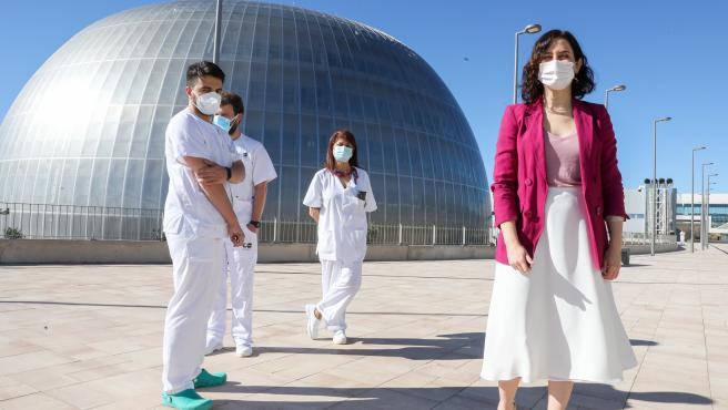 La presidenta de la Comunidad de Madrid, Isabel Díaz Ayuso, junto a varios profesionales sanitarios, durante su visita al inicio del proceso de vacunación contra el COVID-19 que se ha puesto en marcha en el Pabellón 3