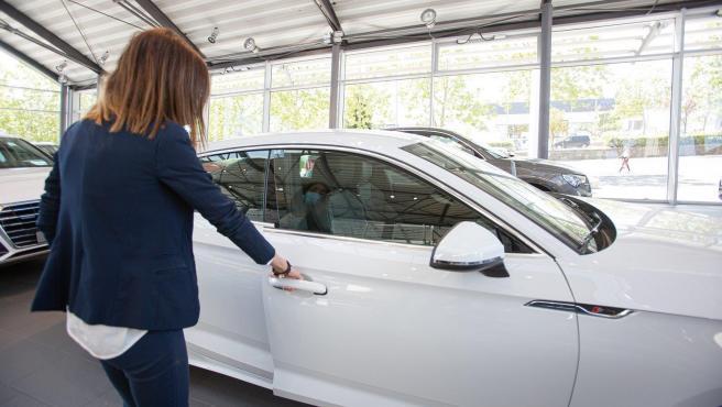 Archivo - Una mujer abre un coche en un concesionario