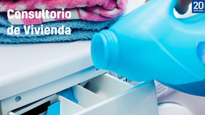 Una persona vierte el detergente en el cajetín de una lavadora.