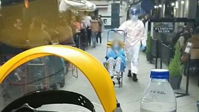 Momento del traslado de la paciente en silla de ruedas hasta la ambulancia.