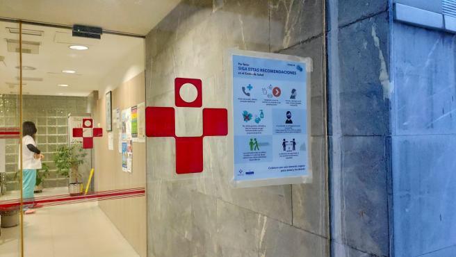 Cartel informativo sobre medidas de seguridad para prevenir el coronavirus, COVID-19, en los centros de Salud. Entrada de Urgencias del Centro de Salud de La Ería, en Oviedo.