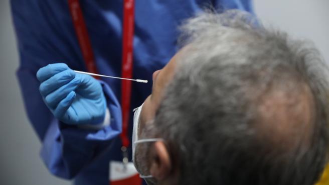 Un sanitario realiza un test de antígenos a un trabajador en la estación de tren de Atocha, Madrid (España), a 22 de febrero de 2021.
