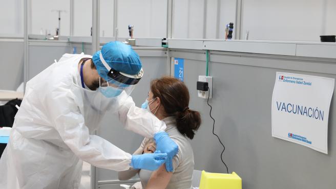 Una mujer recibe la vacuna de AstraZeneca contra el COVID-19, en el Pabellón 3 del Hospital Público Enfermera Isabel Zendal, en Madrid, (España), a 23 de febrero de 2021. Este martes comienza la vacunación en el pabe