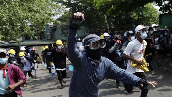 Manifestantes huyen de una carga policial durante protestas contra el golpe militar en Birmania (Myanmar), en Rangún.