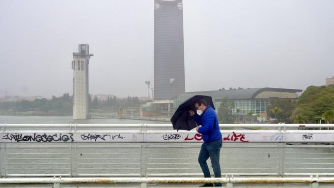 Un persona se protege de la lluvia y el viento caminando por la pasarela peatonal de la Cartuja en Sevilla.