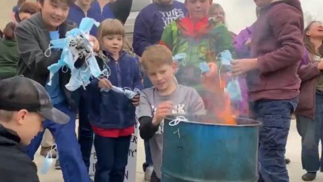 Niños quemando mascarillas quirúrgicas frente al Capitolio de Idaho.