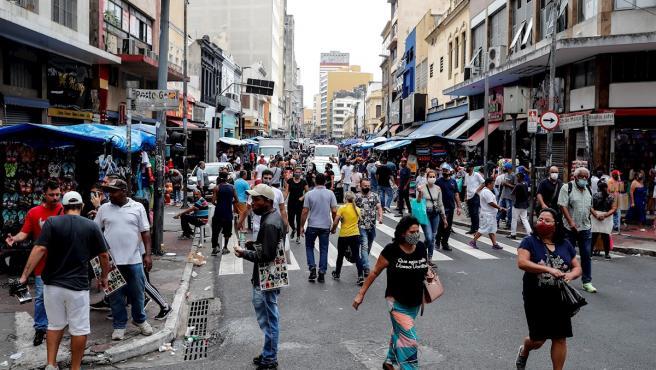 Decenas de personas caminan en una concurrida vía comercial en el centro de Sao Paulo (Brasil).