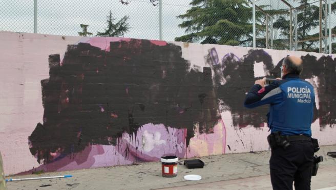 Un policía municipal de Madrid saca una foto al mural, con mujeres famosas, vandalizado con pintura negra, en la entrada de la instalación deportiva del barrido de la Concepción