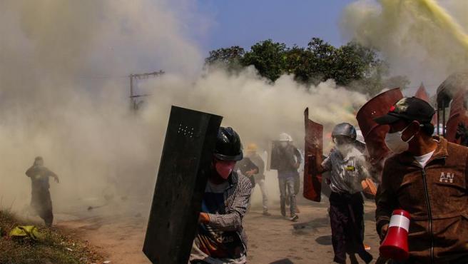 Manifestantes se protegen del gas lacrimógeno lanzado por la policía en Naypidó, Birmania, durante una nueva jornada de protestas contra el golpe militar.