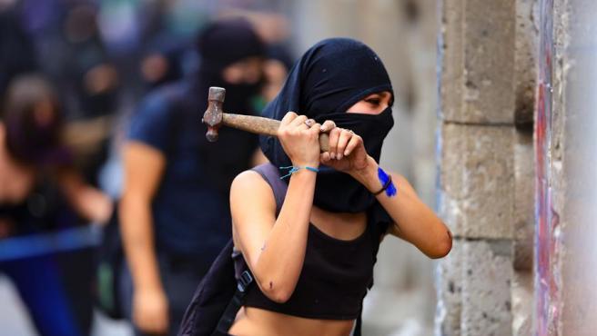 Manifestantes tratan de derribar el muro de protección levantado alrededor del Palacio Nacional, en Ciudad de México, durante las protestas en el Día Internacional de la Mujer.