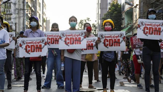 Manifestantes con pancartas del Movimiento de Desobediencia Civil (CDM, por sus siglas en inglés) protestan en Rangún contra el golpe militar en Birmania (Myanmar).
