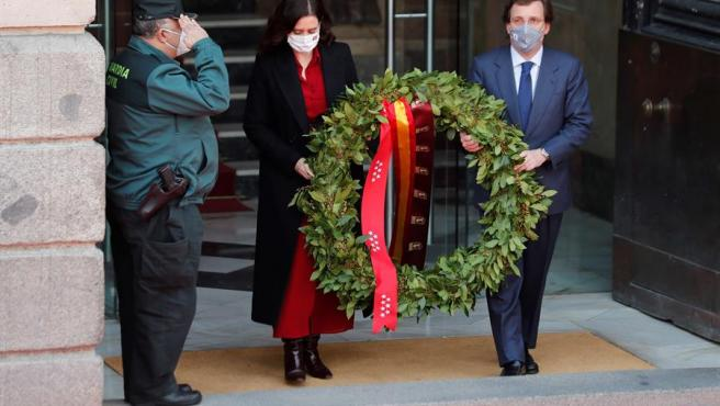 La presidenta de la Comunidad de Madrid, Isabel Díaz Ayuso, y el alcalde de la capital, José Luís Martínez-Almeida (d), llevan una corona durante el acto solemne en recuerdo y homenaje a las víctimas de los atentados del 11 de marzo celebrado este jueves en la Real Casa de Correos, en Madrid