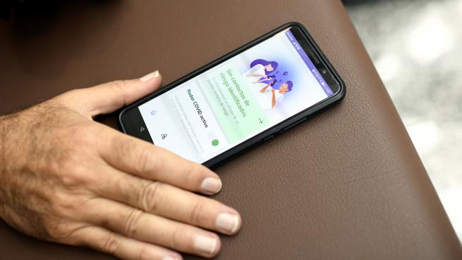 Archivo - Arxive - Una persona utilitza des del seu telèfon mòbil l'aplicació ?Radar Covid?