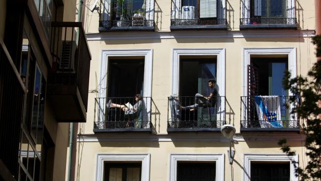 Varios inquilinos toman el sol en sus balcones durante el confinamiento domiciliario por el coronavirus.