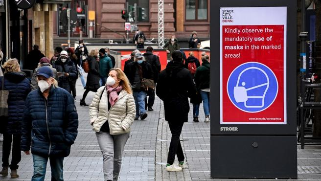 Varios peatones pasan junto a una señal que indica el uso obligatorio de las mascarillas en Bonn, Alemania.