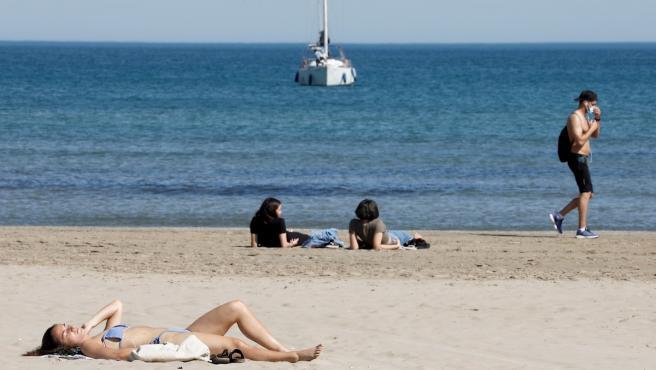 Varias personas toman el sol en la Playa de la Malvarrosa de Valencia.