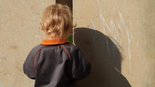 Imagen de archivo de un niño jugando al escondite.