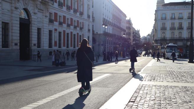 Dos personas utilizando un patinete eléctrico en Madrid.