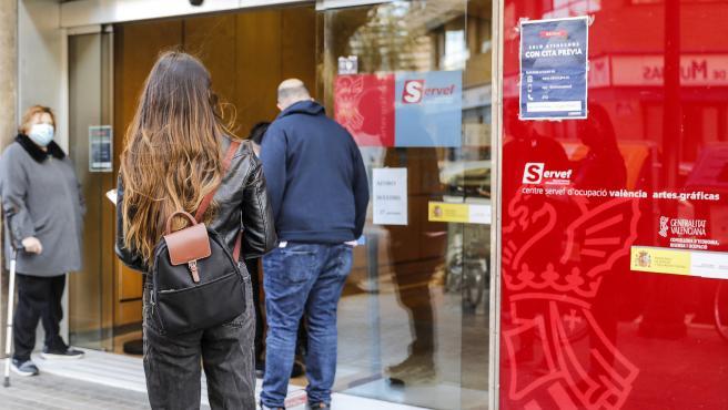 Archivo - Varias personas con cita previa esperan para entrar en una oficina del SEPE