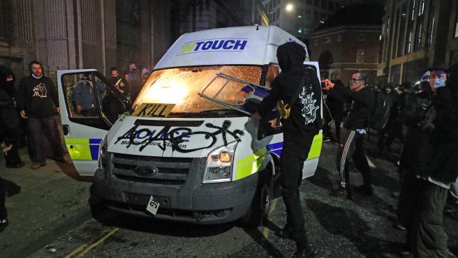 Manifestantes prenden fuego a una furgoneta policial destrozada frente a la estación de policía de Bridewell.