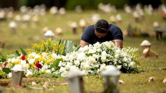Un hombre visita una tumba en un cementerio de Brasilia (Brasil).