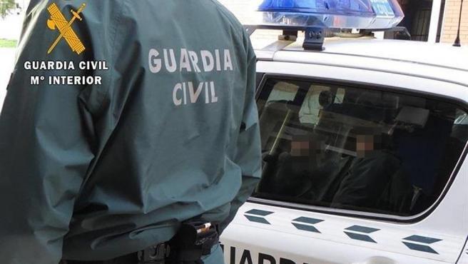 Archivo - Arxive - Un agent de la Guàrdia Civil al costat d'un cotxe patrulla.