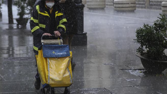 Archivo - Un repartidor de Correos trabaja bajo la lluvia en una foto de archivo