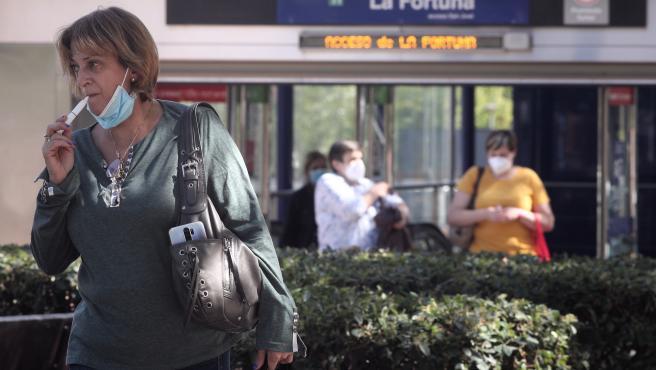 Archivo - Una mujer con un cigarrillo electrónico junto a la parada de Metro La Fortuna en el barrio La Fortuna de Leganés, en Madrid