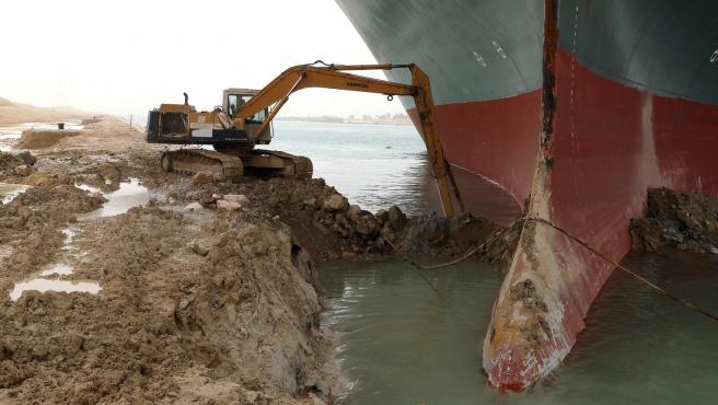 Una excavadora horada el terreno para liberar al buque Ever Given, encallado en el Canal de Suez.