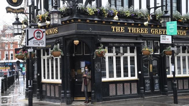 Una persona con mascarilla apoyada en la puerta de un pub cerrado en Londres este jueves.
