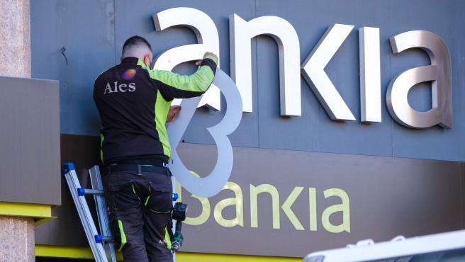Un operario retira el rótulo de Bankia de la sede principal del banco en Logroño este sábado.