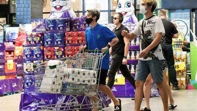 Varias personas realizan compras en un supermercado en Brisbane, Australia, antes del inicio de un confinamiento en la ciudad por la detección de nuevos casos de coronavirus.