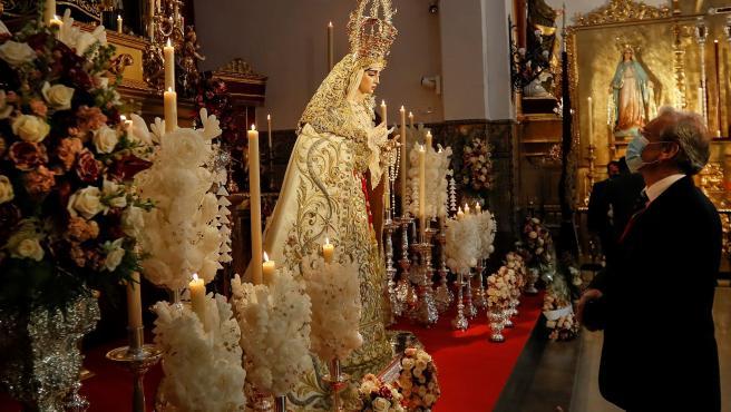 Un hombre observa a la Virgen de Nuestra Señora de la Salud, de la Hermandad de San Gonzalo, en el interior de la iglesia.