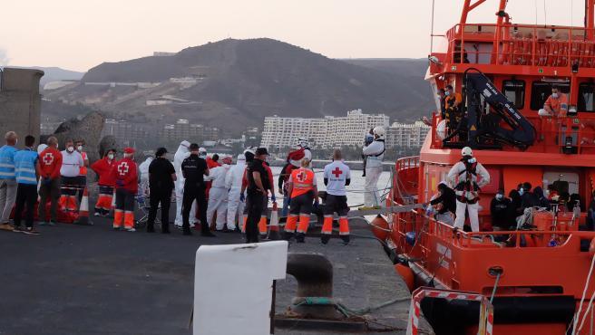 MIembros de la Cruz Roja ayudan a bajar del barco a migrantes en el puerto de Arguineguín (foto recurso)