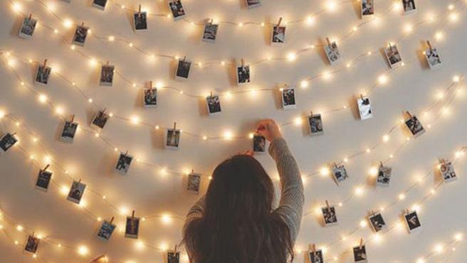Fotografías de pequeño formato colgadas en guirnalda de luces LED.