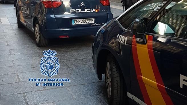 Archivo - Agentes de la Policía Nacional junto a dos coches patrulla