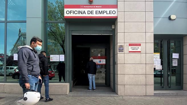 Varias personas esperan en las frente a una oficina del SEPE.
