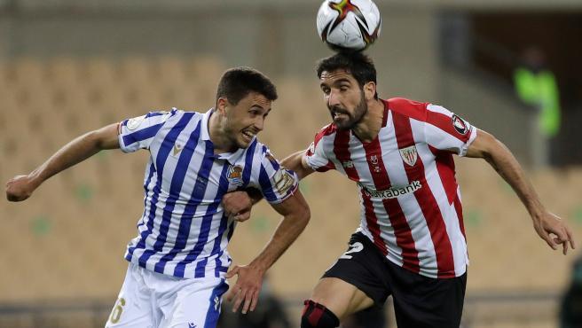 Martín Zubimendi (i) y Raúl García (d) pugnan por un balón durante el Real Sociedad - Athletic